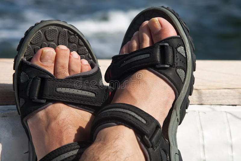 Feet on a Boat. A pair of male feet on the stern of a boat with ocean in the background stock photography