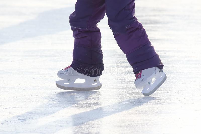 Feet of a child skating on an ice rink. The feet of a child skating on an ice rink stock images