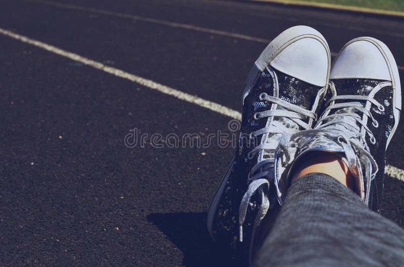 Feet crossed in shoes on track. Person wearing black and white high top shoes, with ankles and feet crossed while sitting on a track. Casual wear for athleisure royalty free stock photography