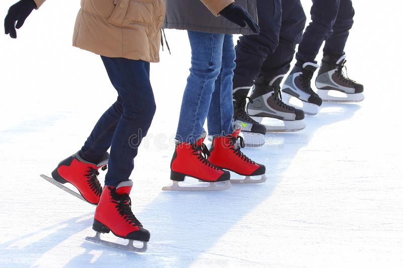 Feet of different people skating on the ice rink. The feet of different people skating on the ice rink stock image