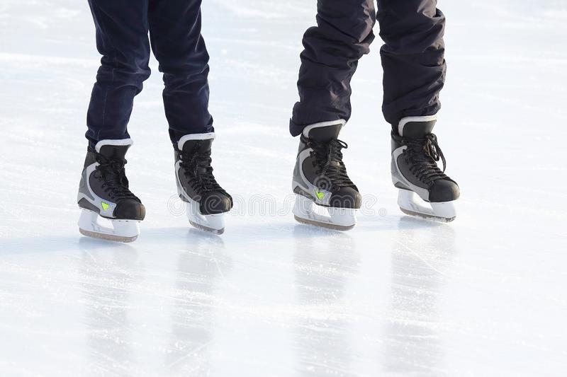Feet of different people skating on the ice rink. The feet of different people skating on the ice rink stock photo