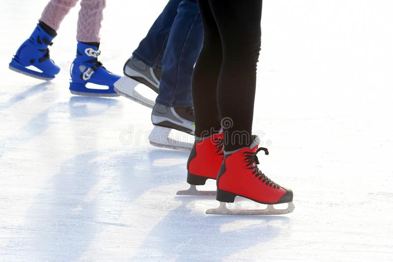 Feet of different people skating on the ice rink. The feet of different people skating on the ice rink stock photography