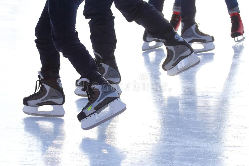 Feet of different people skating on the ice rink. The feet of different people skating on the ice rink. sports, Hobbies and recreation of active people royalty free stock photos