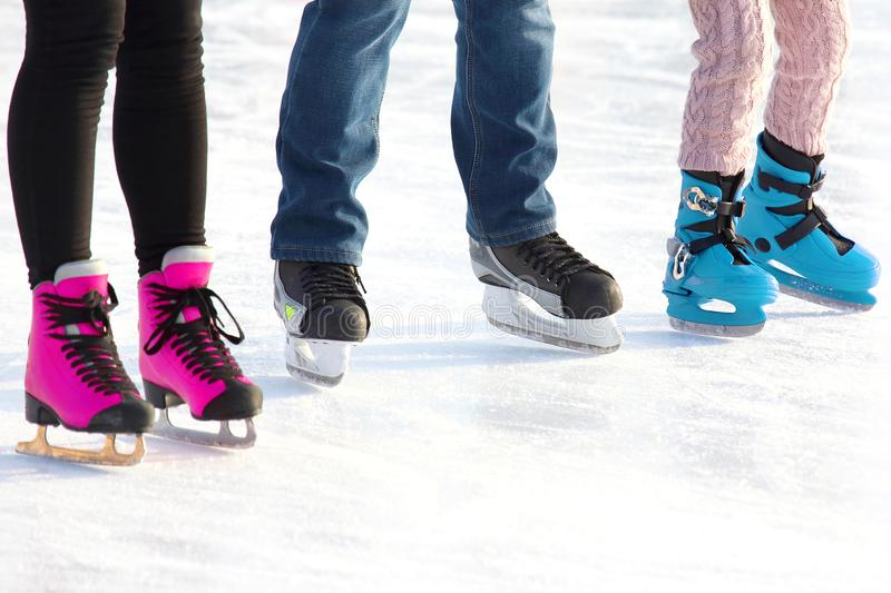 Feet of different people skating on the ice rink. sports, Hobbies and recreation of active people. The feet of different people skating on the ice rink. sports royalty free stock photography