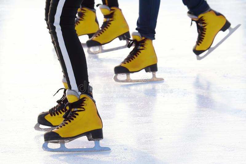 Feet of different people skating on the ice rink. sports, Hobbies and recreation of active people. The feet of different people skating on the ice rink. sports stock photo