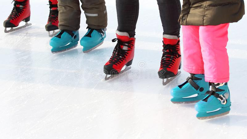Feet of different people skating on the ice rink. The feet of different people skating on the ice rink. sports, Hobbies and recreation of active people royalty free stock images