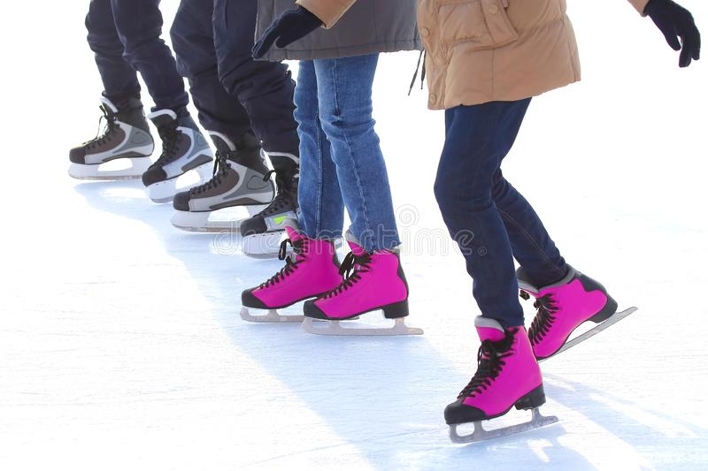 Feet of different people skating on the ice rink. Sports, Hobbies and recreation of active people royalty free stock images