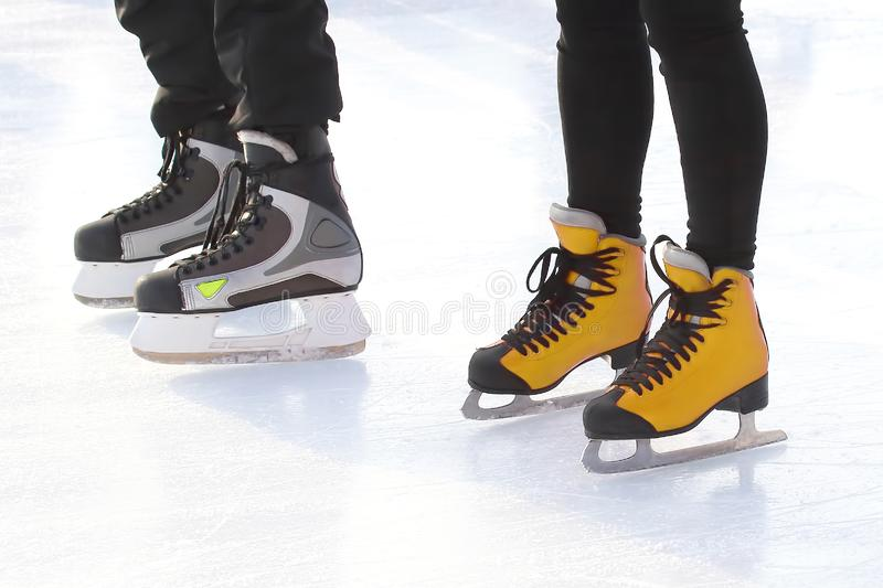Feet of different people skating on the ice rink. Sports, Hobbies and recreation of active people royalty free stock photo