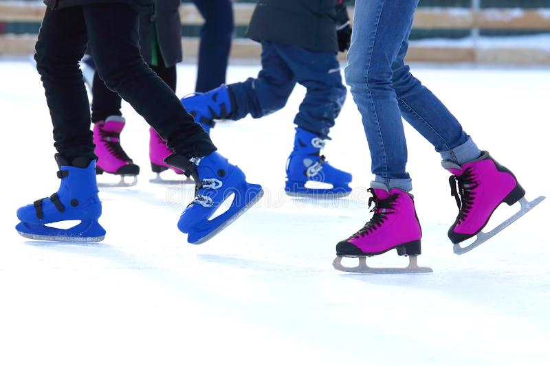 Feet of different people skating on the ice rink. The feet of different people skating on the ice rink. sports, Hobbies and recreation of active people stock images