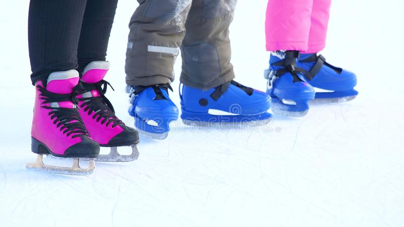 Feet of different people skating on the ice rink. Sports, Hobbies and recreation of active people royalty free stock photos