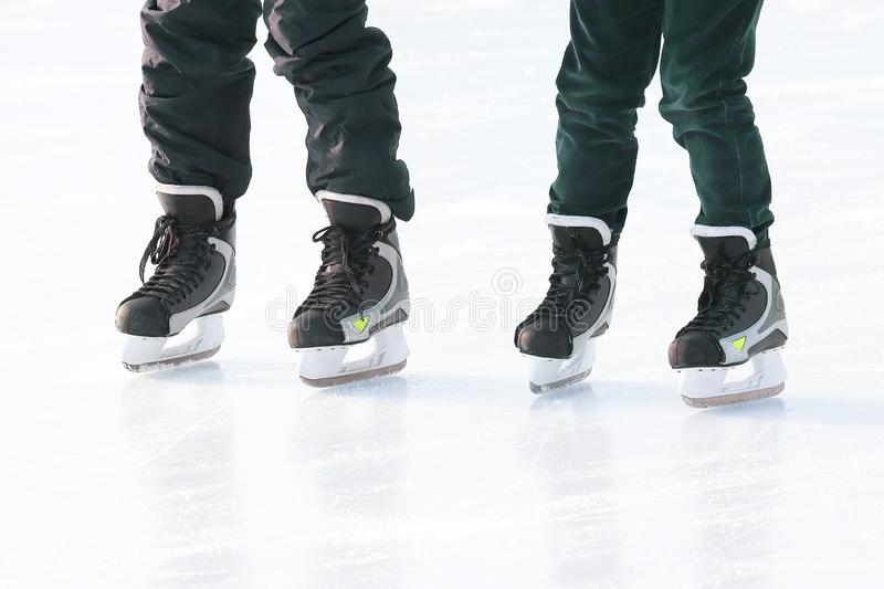 Feet of different people skating on the ice rink. Vacation sports and hobbies stock images