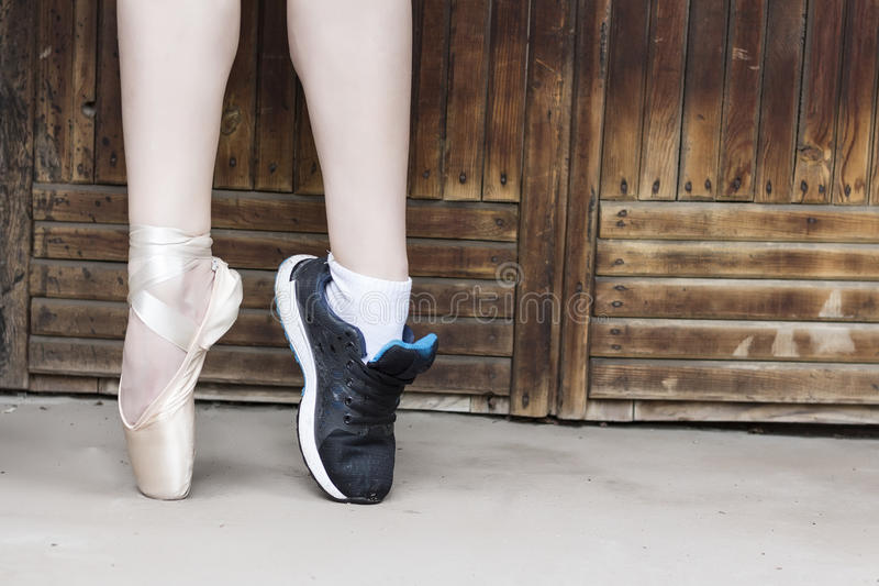 Feet dressed in dance pointe shoes and sports shoes royalty free stock images