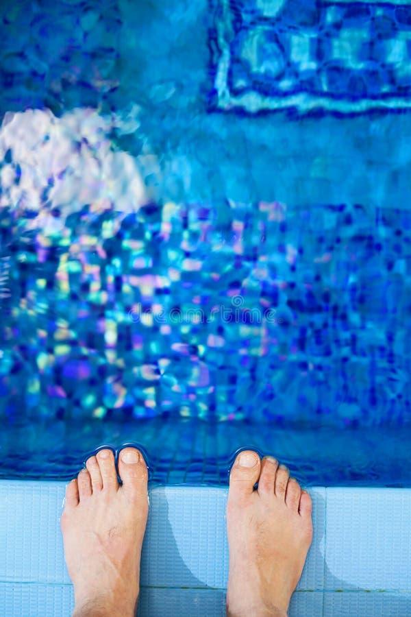 Feet on the edge of the pool stock photos