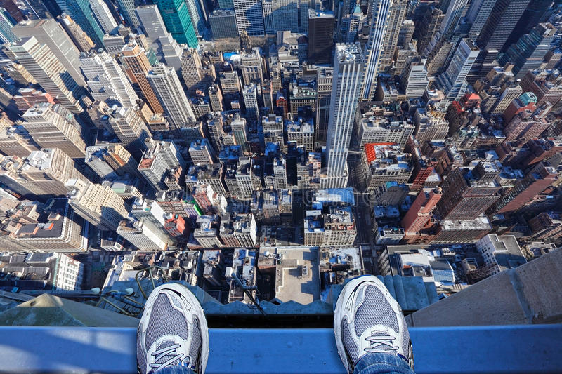 Feet on the edge of tall building. Jumpers feet on the edge of a very tall building thinking of committing suicide, depression, stress concept. Empire State