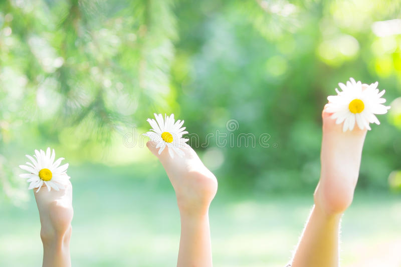 Feet of family with flowers. Against green spring background royalty free stock photography
