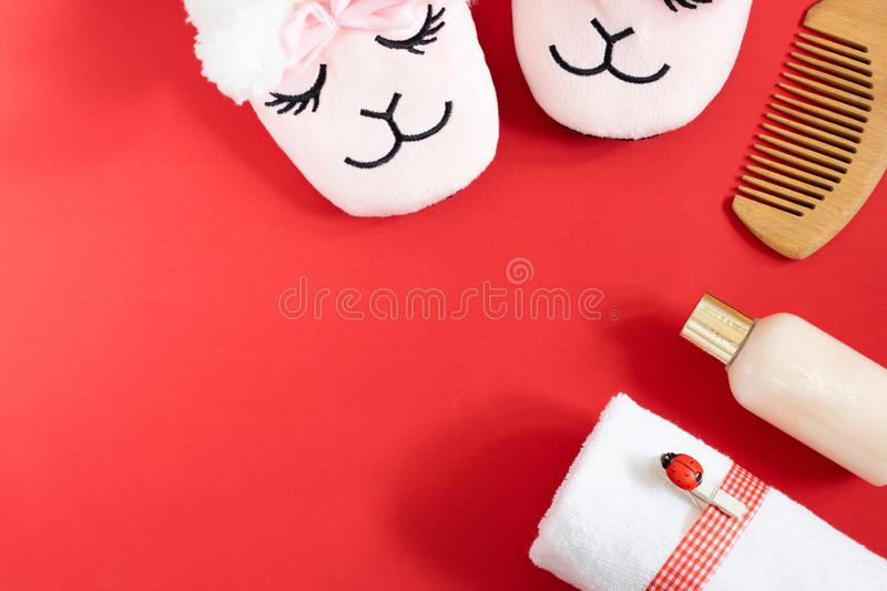 Feet female cute sleeping pink lama trendy slippers, bottle of bath foam, white towel with ribbon and ladybird pin royalty free stock photo