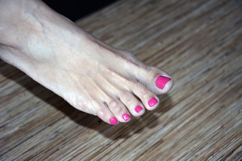 Feet of a female leg with nails painted in red lacquer. Homemade pedicure stock image
