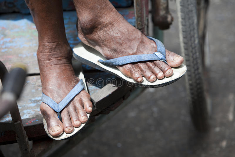 Feet in Flip-Flops On a Delivery Cart. Cropped close-up of a senior's feet wearing flip-flops on a delivery cart. Horizontal format stock image