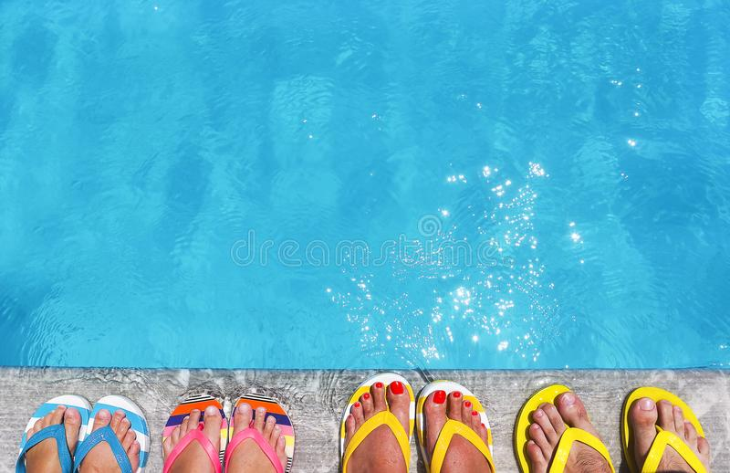 Feet in flip flops on stone background. On poolside. Summer family vacation concept stock images