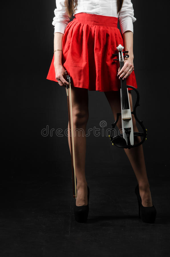 Feet girl in a skirt with a violin royalty free stock photo