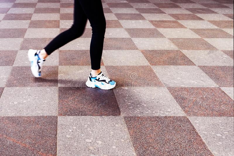 Feet girl in sneakers, walking on a stone tile royalty free stock image