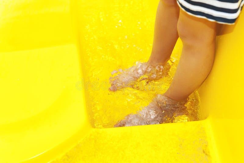 Feet of girls standing in bucket stock photo