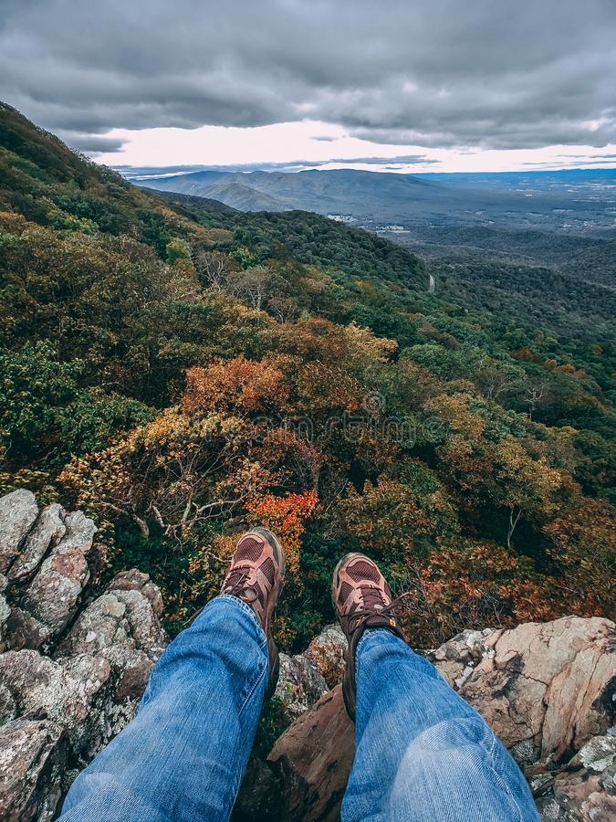 Feet hang over the edge of a cliff overlooking a valley filled with Autumn colors. royalty free stock images