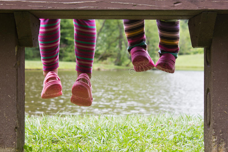Feet hanging from a bench stock photos