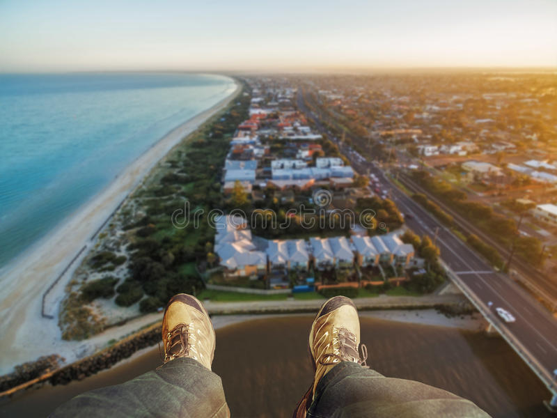 Feet hanging out of helicopter above Patterson Lakes suburb and. Nepean Highway at sunrise. Melbourne, Victoria, Australia stock photo