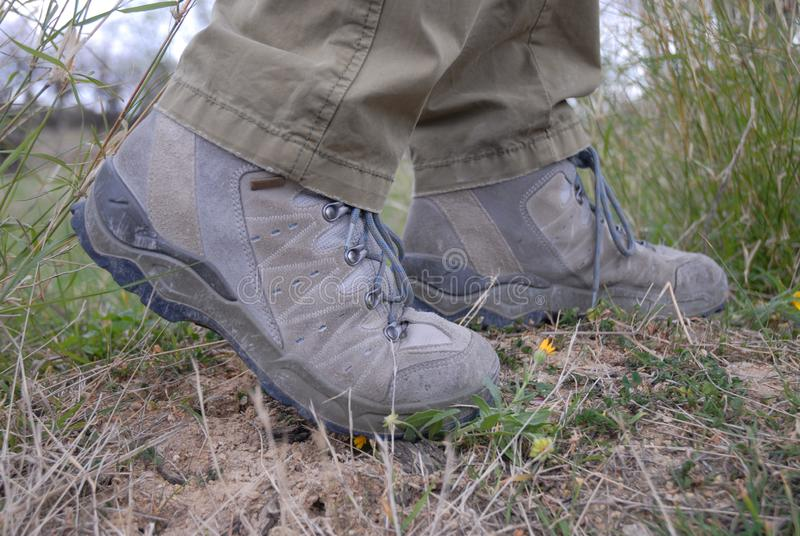 Feet in hiking boots, low angle view. Person walking outdoors in sturdy hiking boots, concept of healthy lifestyle and keeping fit stock photography