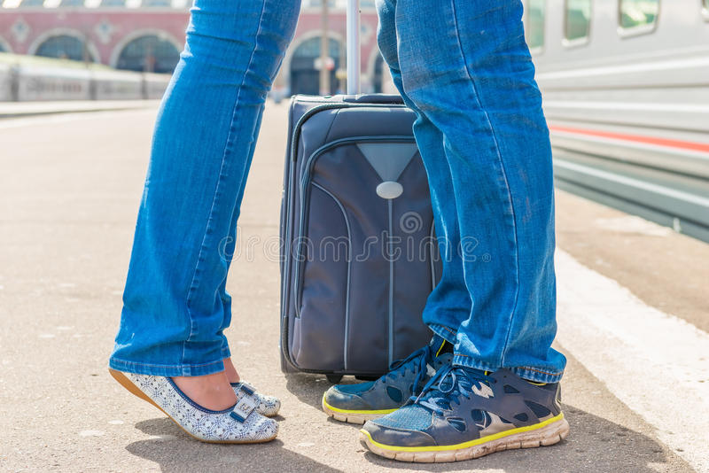 Feet kissing couple near a suitcase. At the railway station close-up stock photos
