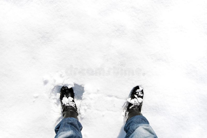 Feet in leather boots in deep snow on sunny winter weather stock images