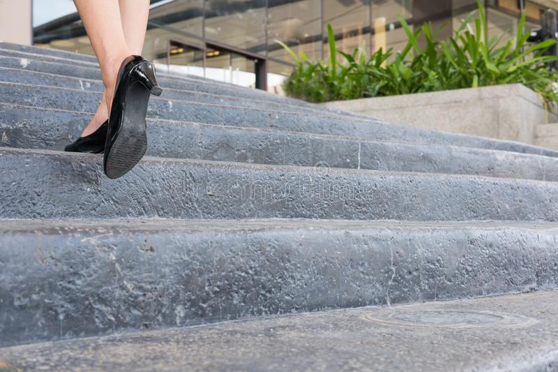 Feet and leg of businesswoman wearing black high heel shoes going up the stairs outdoors. woman go to work at office. Feet and leg of businesswoman wearing royalty free stock photography