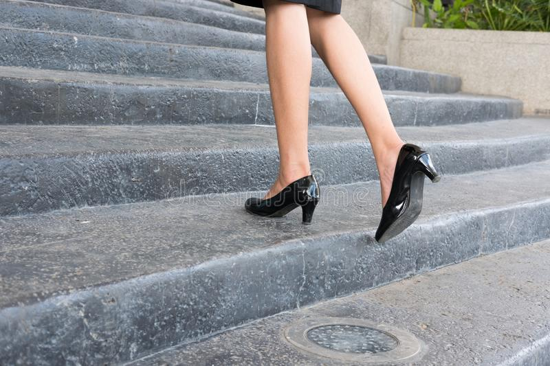 Feet and leg of businesswoman wearing black high heel shoes going up the stairs outdoors. woman go to work at office. Feet and leg of businesswoman wearing royalty free stock photo