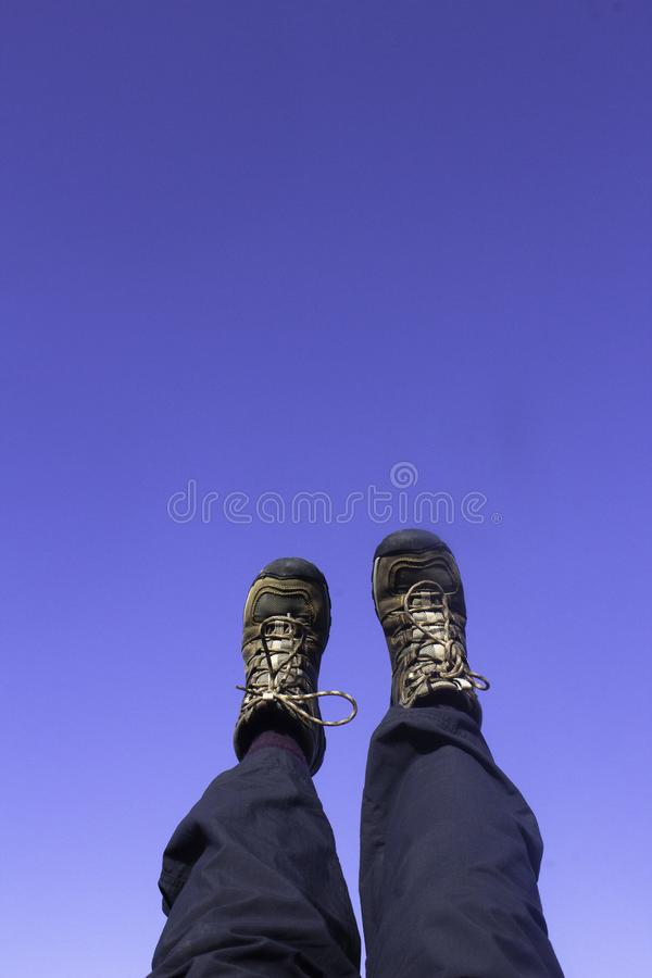 Feet and legs in brown hiking boots and blue hiking pants against a clear blue sky. With copy space royalty free stock photography