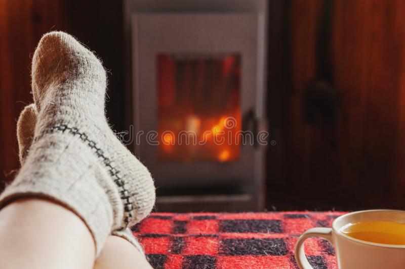 Feet legs in winter clothes wool socks and cup tea at fireplace at home on winter or autumn evening relaxing and warming up. Feet legs in winter clothes wool stock photography