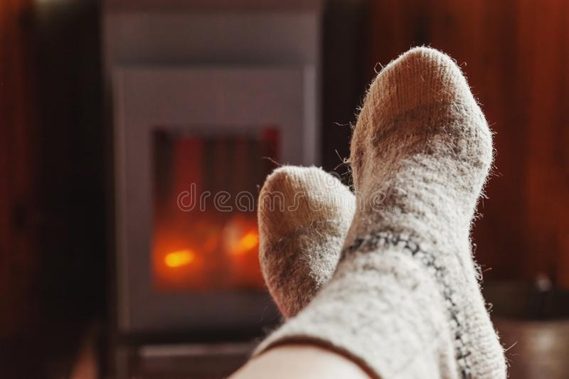 Feet legs in winter clothes wool socks at fireplace at home on winter or autumn evening relaxing and warming up. Feet legs in winter clothes wool socks at royalty free stock photos