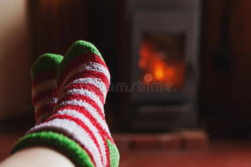 Feet legs in winter clothes wool socks at fireplace at home on winter or autumn evening relaxing and warming up. Feet legs in winter clothes wool socks at stock photography