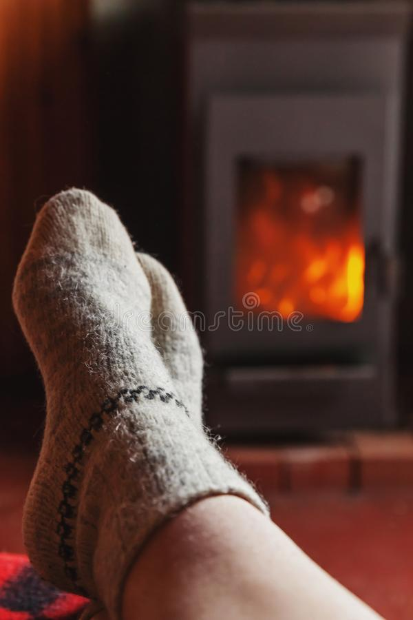 Feet legs in winter clothes wool socks at fireplace at home on winter or autumn evening relaxing and warming up. Feet legs in winter clothes wool socks at stock image