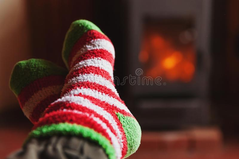 Feet legs in winter clothes wool socks at fireplace at home on winter or autumn evening relaxing and warming up. Feet legs in winter clothes wool socks at stock images