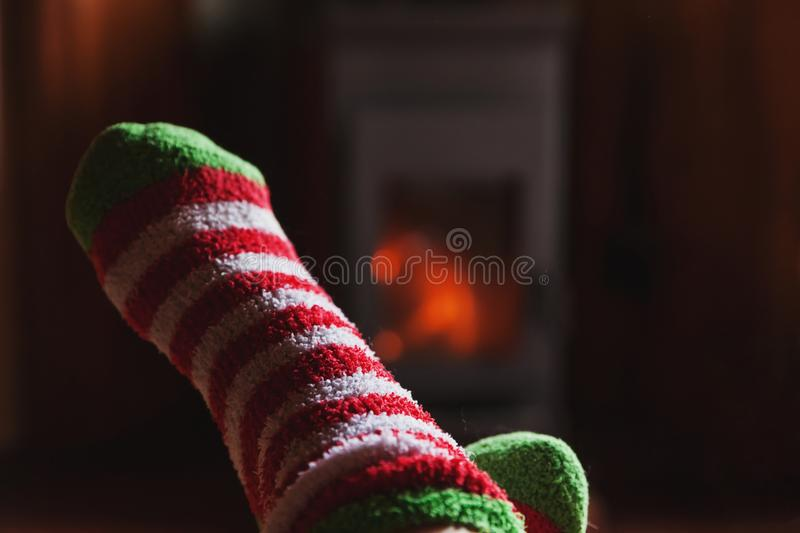 Feet legs in winter clothes wool socks at fireplace at home on winter or autumn evening relaxing and warming up. Feet legs in winter clothes wool socks at stock photo