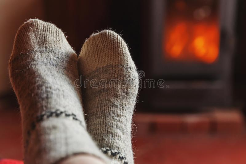 Feet legs in winter clothes wool socks at fireplace at home on winter or autumn evening relaxing and warming up. Feet legs in winter clothes wool socks at royalty free stock images