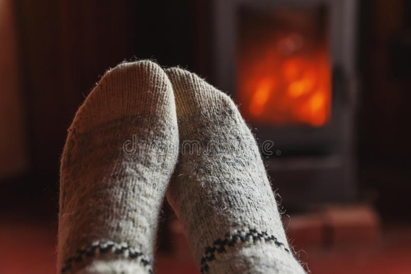 Feet legs in winter clothes wool socks at fireplace at home on winter or autumn evening relaxing and warming up. Feet legs in winter clothes wool socks at royalty free stock photography