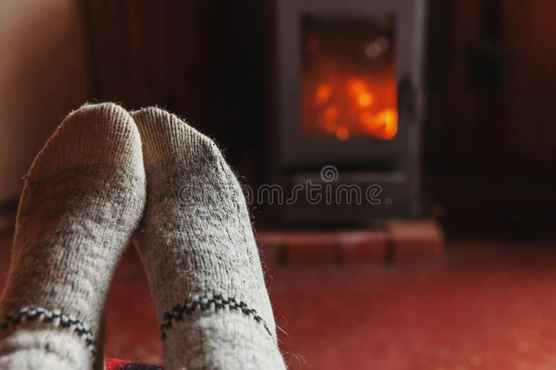 Feet legs in winter clothes wool socks at fireplace at home on winter or autumn evening relaxing and warming up. Feet legs in winter clothes wool socks at royalty free stock image