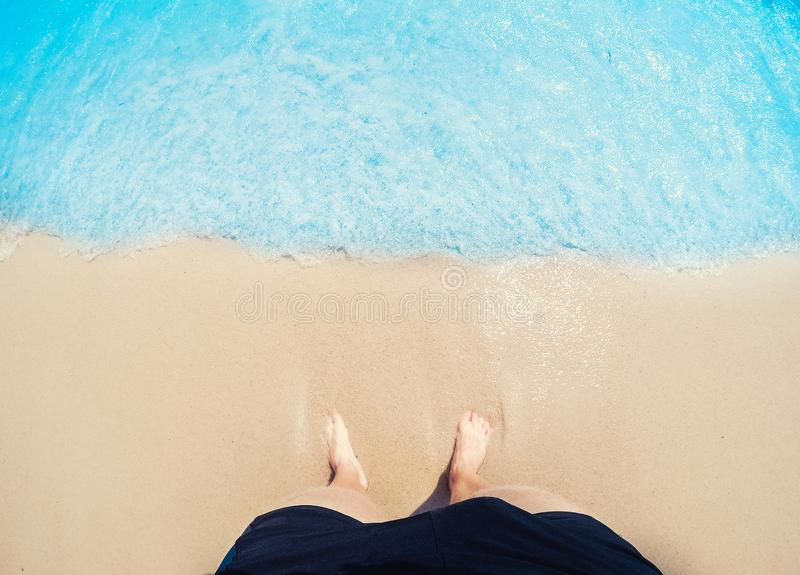 Feet of man foot in golden sand are washed by waves of blue sea, top view. Freelance travel freelancer concept stock image