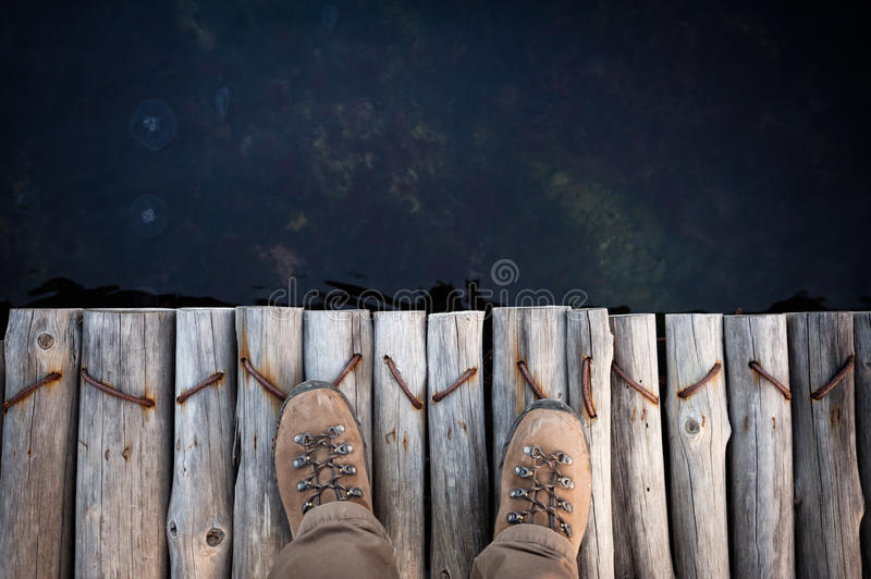 Feet of man in hiking boots. On a wooden bridge stock image