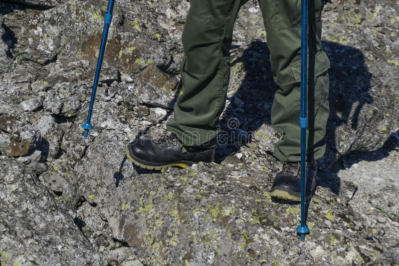 Feet in hiking boots in the natural landscape. Feet of a man in hiking boots with trekking poles walking in a rocky landscape royalty free stock images