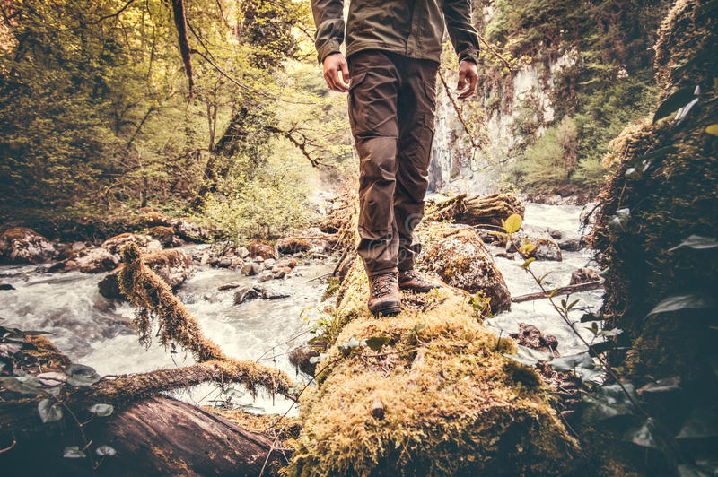 Feet Man hiking outdoor. With river and forest on background Lifestyle Travel survival concept stock image