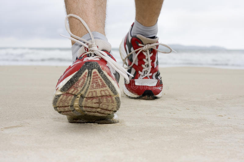 Feet of man jogging on a beach stock photos