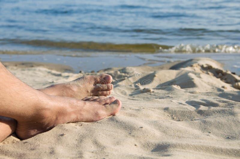 The feet of man lie on sand